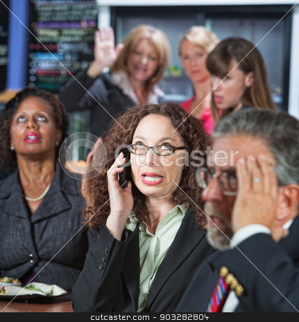 Loud Coworker on Phone stock photo, Loud woman on cell phone in cafeteria with coworkers by Scott Griessel