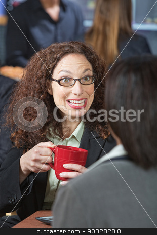 Woman Talking to Friend stock photo, Happy business woman with red mug talking to friend by Scott Griessel
