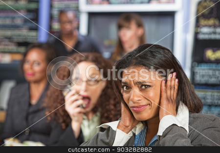Loud Person on Phone stock photo, Bothered business person covering ears while person talks by Scott Griessel