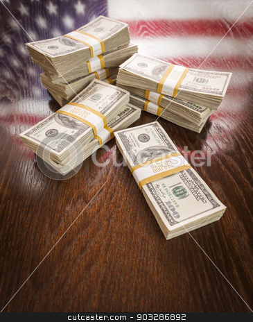 Thousands of Dollars with Reflection of American Flag on Table stock photo, Thousands of Dollars Stacked with Reflection of American Flag on Wooden Table. by Andy Dean