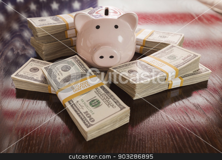 Thousands of Dollars, Piggy Bank, American Flag Reflection on Ta stock photo, Thousands of Dollars and Piggy Bank with Reflection of American Flag on Table. by Andy Dean