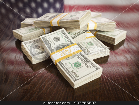 Thousands of Dollars with Reflection of American Flag on Table stock photo, Thousands of Dollars Pile with Reflection of American Flag on Wooden Table. by Andy Dean