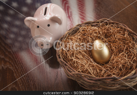 Golden Egg, Nest and Piggy Bank with American Flag Reflection stock photo, Golden Egg in Nest and Piggy Bank with American Flag Reflection on Wooden Table. by Andy Dean