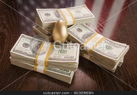 Golden Egg and Thousands of Dollars with American Flag Reflectio stock photo, Golden Egg and Thousands of Dollars with American Flag Reflection on Table. by Andy Dean