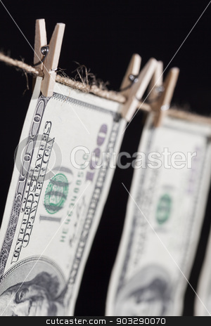 Hundred Dollar Bills Hanging From Clothesline on Dark Background stock photo, Hundred Dollar Bills Hanging From a Clothesline on a Dark Background. by Andy Dean