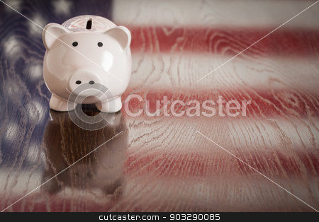 Piggy Bank with an American Flag Reflection on Table stock photo, Piggy Bank with an American Flag Reflection on Wooden Table. by Andy Dean