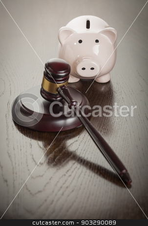 Gavel and Piggy Bank on Table stock photo, Gavel and Piggy Bank on Reflective Wooden Table. by Andy Dean