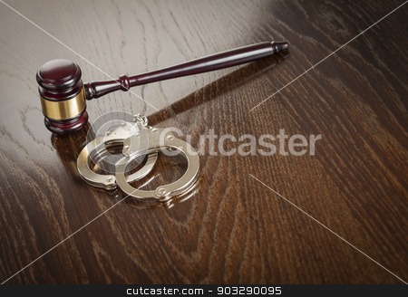 Gavel and Pair of Handcuffs on Table stock photo, Gavel and Pair of Handcuffs on Wooden Table. by Andy Dean