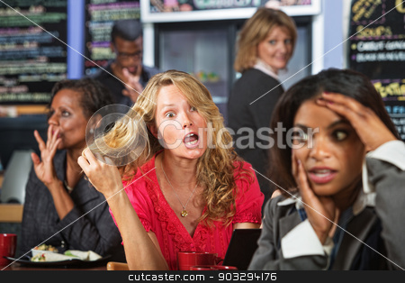 Overreacting Young Woman stock photo, Emotional woman pulling hair in cafe with embarrassed friend by Scott Griessel