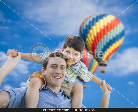 Father and Son Playing Piggyback with Hot Air Balloons Behind stock photo, Father and Son Playing Piggyback with Hot Air Balloons Floating Behind Them. by Andy Dean