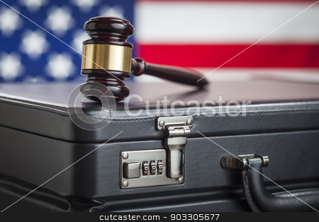 Briefcase and Gavel Resting on Table with American Flag Behind stock photo, Leather Briefcase and Gavel Resting on Table with American Flag Behind. by Andy Dean