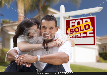 Hispanic Couple, New Home and Sold Real Estate Sign stock photo, Young Happy Hispanic Young Couple in Front of Their New Home and Sold For Sale Real Estate Sign. by Andy Dean