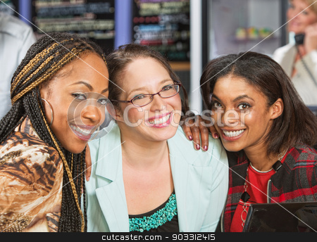 Trio of Smiling Friends stock photo, Diverse group of three young women in cafe by Scott Griessel