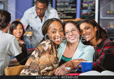 Trio of Smiling Friends stock photo, Trio of smiling young friends in cafe by Scott Griessel
