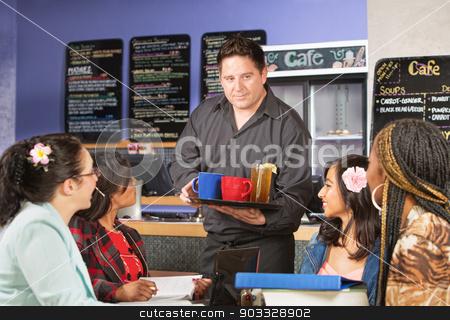 Barista Serving Beverages stock photo, Cheerful barista serving beverages to students in cafe by Scott Griessel