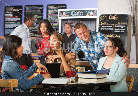 Flirting with Students stock photo, Smiling man flirting with female students in coffee house by Scott Griessel