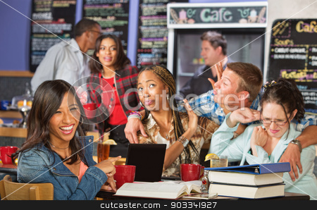 Laughing at Flirting Man stock photo, Student laughing at friends reaction to kissing man in cafe by Scott Griessel