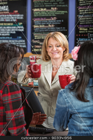 Woman Serving Drinks stock photo, Smiling cafe owner serving drinks to customers by Scott Griessel