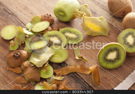 Preparing a tropical kiwifruit dessert stock photo, Preparing a tropical kiwifruit dessert with a high angle view of peels, peeled kiwi fruit and sliced fruit being prepared in a rustic country kitchen by Stephen Gibson