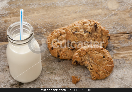 Bottle of milk with half eaten cookies stock photo, Small glass bottle of fresh creamy farm milk with a straw alongside half eaten crunchy cookies on a rustic wooden surface, high angle view by Stephen Gibson