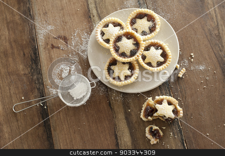 Decorative freshly baked Christmas mince pies stock photo, Overhead view of a plate of decorative freshly baked Christmas mince pies with pastry stars alongside a half eaten pie and strainer with icing sugar to dust the top by Stephen Gibson
