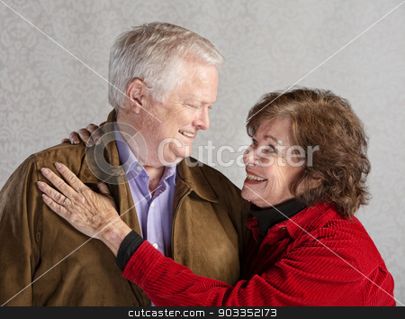 Caring Couple Embracing stock photo, Senior husband and wife looking in each others eyes by Scott Griessel