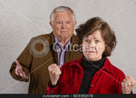 Offended Senior Woman stock photo, Offended mature wife near frustrated husband with hands up by Scott Griessel