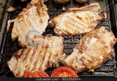 Grilled pork chops and tomatoes on a griddle stock photo, Grilled pork chops and tomatoes on a griddle ready to be served for a tasty luch or dinner, high angle view by Stephen Gibson