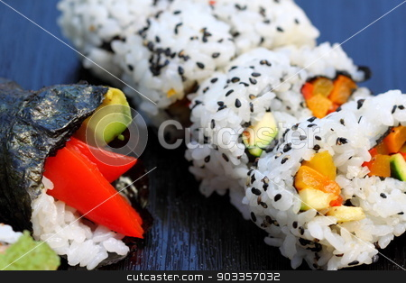 Sushi stock photo, California sushi roll platted on a black plate. by Henrik Lehnerer