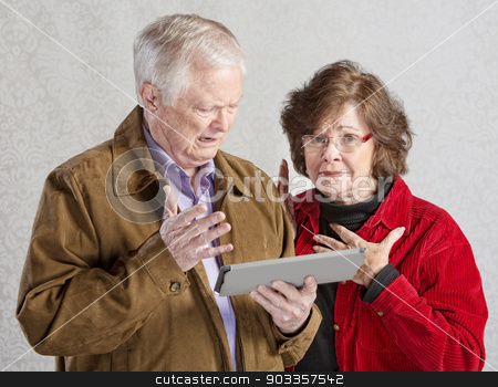 Senior Couple with Tablet stock photo, Overwhelmed senior man and woman holding tablet by Scott Griessel