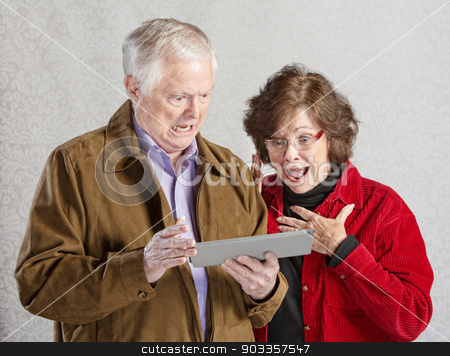 Shocked Couple with Tablet stock photo, Shocked man and woman looking at computer tablet by Scott Griessel