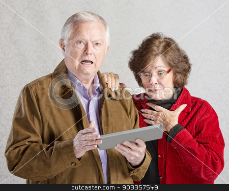 Startled Couple with Tablet stock photo, Startled man and woman looking at computer tablet by Scott Griessel