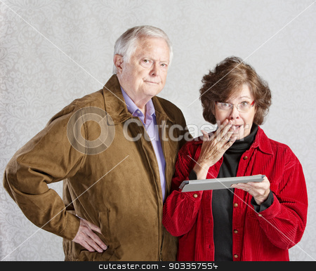 Embarrassed Woman with Tablet stock photo, Suspicious man and embarrassed woman holding tablet by Scott Griessel