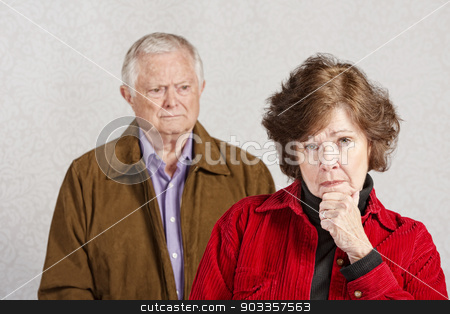 Serious Senior Woman stock photo, Serious woman with hand on chin with man watching by Scott Griessel