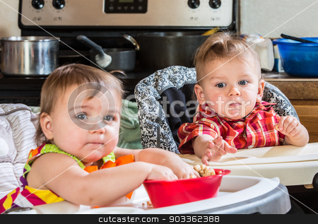 Baby Reaches for Cereal stock photo, A baby reaches out to get his sisters cereal by Scott Griessel