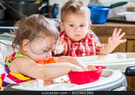 Two Babies Eat Breakfast stock photo, Two cute babies are eating breakfast together by Scott Griessel