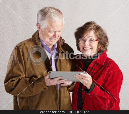 Happy Couple with Tablet stock photo, Happy older man and woman holding a tablet computer by Scott Griessel