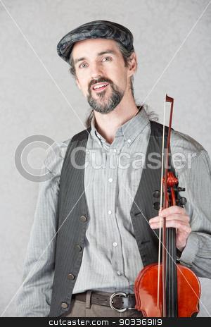Cheerful Irish Fiddler with Instrument stock photo, One cheerful Irish fiddler with violin and bow by Scott Griessel