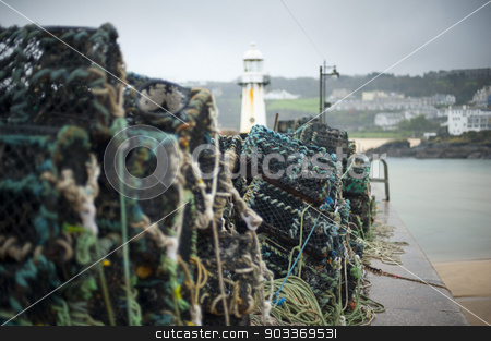 Fishing at St Ives harbor stock photo, Fishing at St Ives harbor with a view past a stack of old wire lobster or crab traps to the lighthouse at the harbor entrance by Stephen Gibson