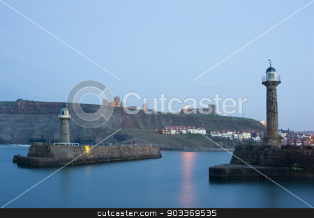 Two breakwater navigation beacons stock photo, Two breakwater navigation beacons on the ends of the piers on either side of the entrance to Whitby harbour at dusk with St Marys Church and Whitby Abbey visible on Tate Hill in the distance by Stephen Gibson