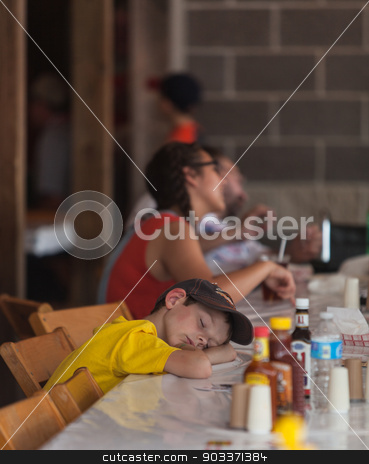 Tired Boy at Iowa State Fair stock photo, DES MOINES, IA /USA - AUGUST 10: Unidentified tired boy rests head on table at the Iowa State Fair on August 10, 2014 in Des Moines, Iowa, USA. by Scott Griessel