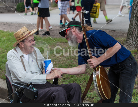 Banjo Player with Man in Wheelchair at Iowa State Fair stock photo, DES MOINES, IA /USA - AUGUST 10: Unidentified banjo player shakes hand at the Iowa State Fair on August 10, 2014 in Des Moines, Iowa, USA. by Scott Griessel