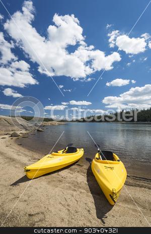 Pair of Yellow Kayaks on Beautiful Mountain Lake Shore. stock photo, Pair of Yellow Kayaks on a Beautiful Mountain Lake Shore. by Andy Dean