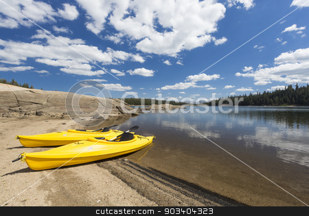 Pair of Yellow Kayaks on Beautiful Mountain Lake Shore. stock photo, Pair of Yellow Kayaks on a Beautiful Mountain Lake Shore. by Andy Dean