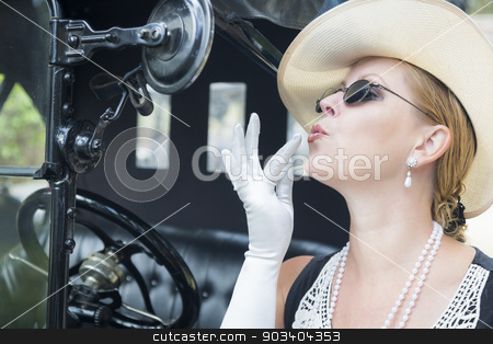 Attractive Woman in Twenties Outfit Checking Makeup in Antique A stock photo, Attractive Young Woman in Twenties Outfit Checking Makeup in Antique Automobile. by Andy Dean