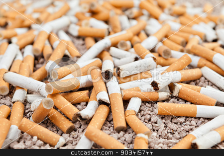 Fallen cigarettes chaos stock photo, Ashtray full of fallen smoked cigarettes in the sand  by Dario Rota