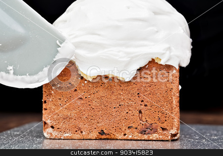 Spreading cream on cake with spatula stock photo, Spreading cream on christmas cake icing with spatula  by Dario Rota