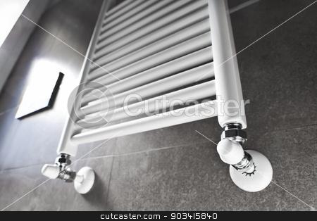 Bathroom heater with window stock photo, White bathroom heater lighted by the window  by Dario Rota