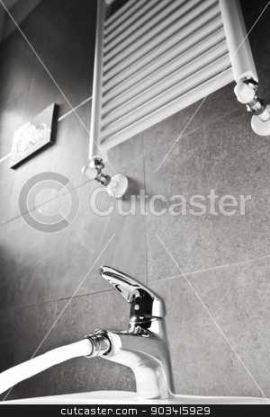 Faucet with water and heater stock photo, Bathroom faucet with water and heater on a gray wall  by Dario Rota