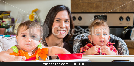 Mother Smiles With Babies stock photo, A mother in the kitchen poses with babies by Scott Griessel